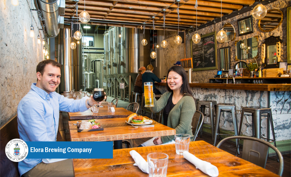 two people raising glasses of beer inside brewery