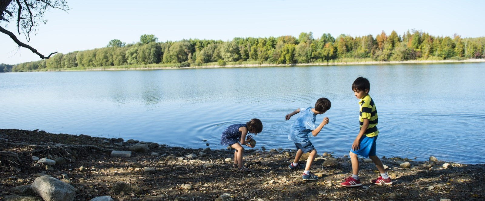 three kids skipping rocks on a lake
