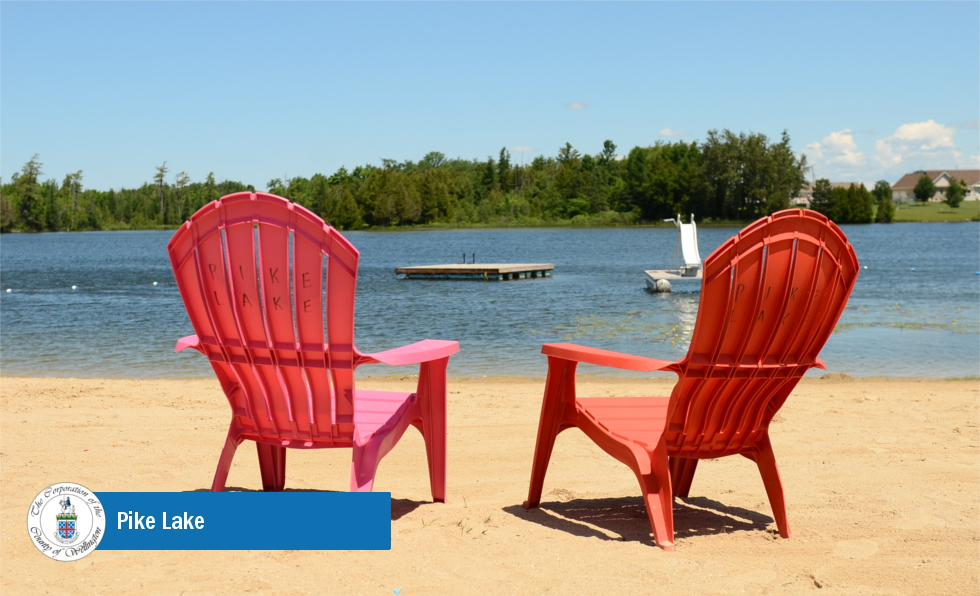 Two red lounge chairs on sand facing water
