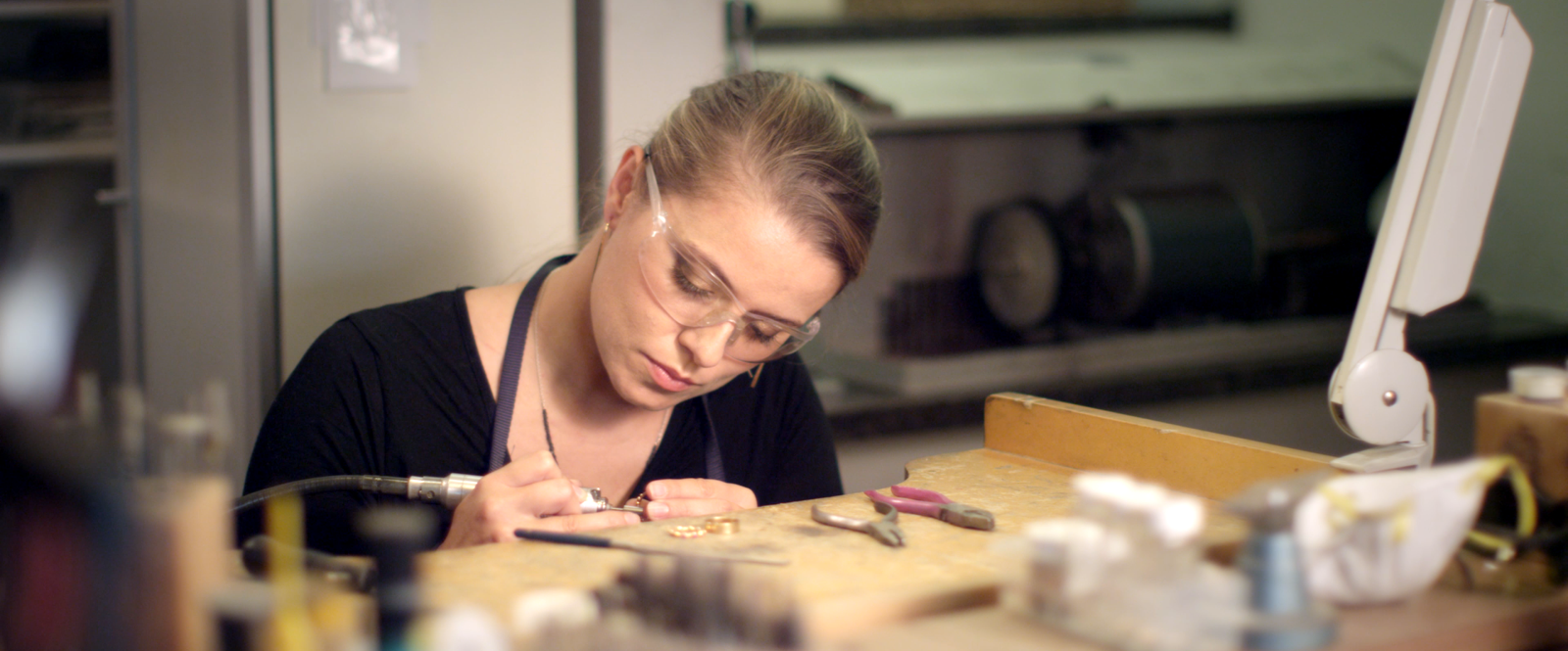Jeweller making rings at her workstation