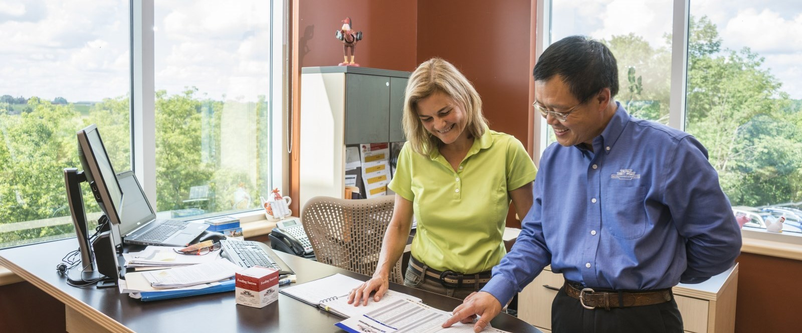 Two people looking at reports in the Wallenstein Feed Supply office