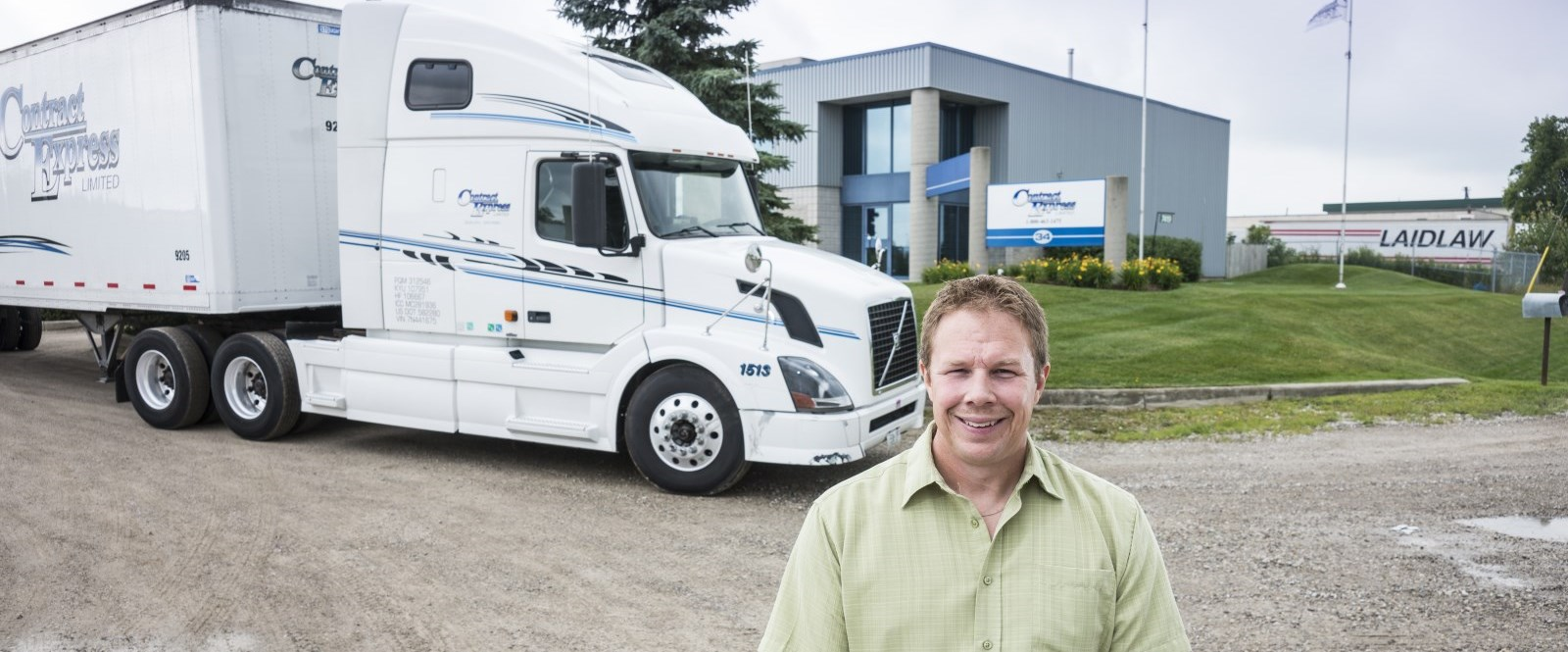 portrait of a working in front of a truck at Contract Express