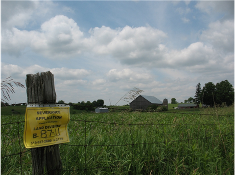 Severance notice sign on fence post sitting in front of farm