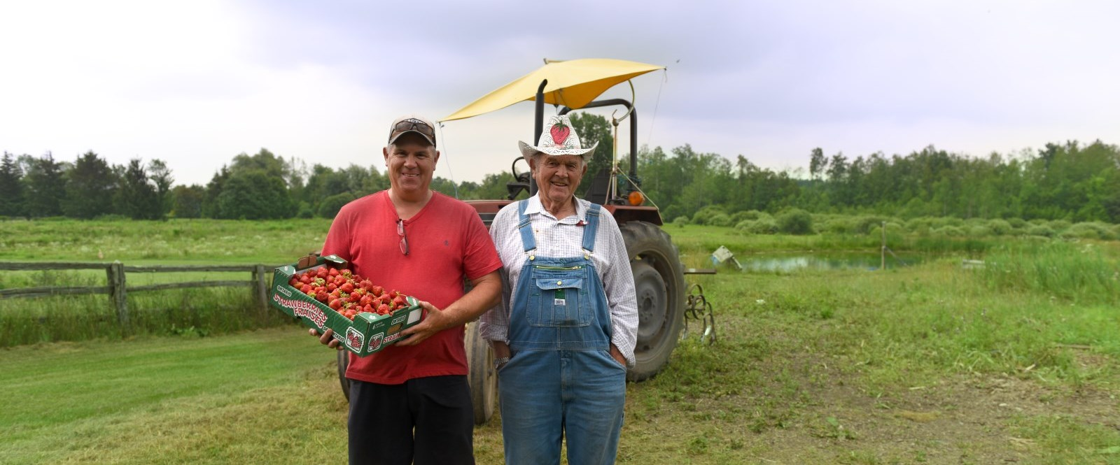 two strawberry farmers standing in a field