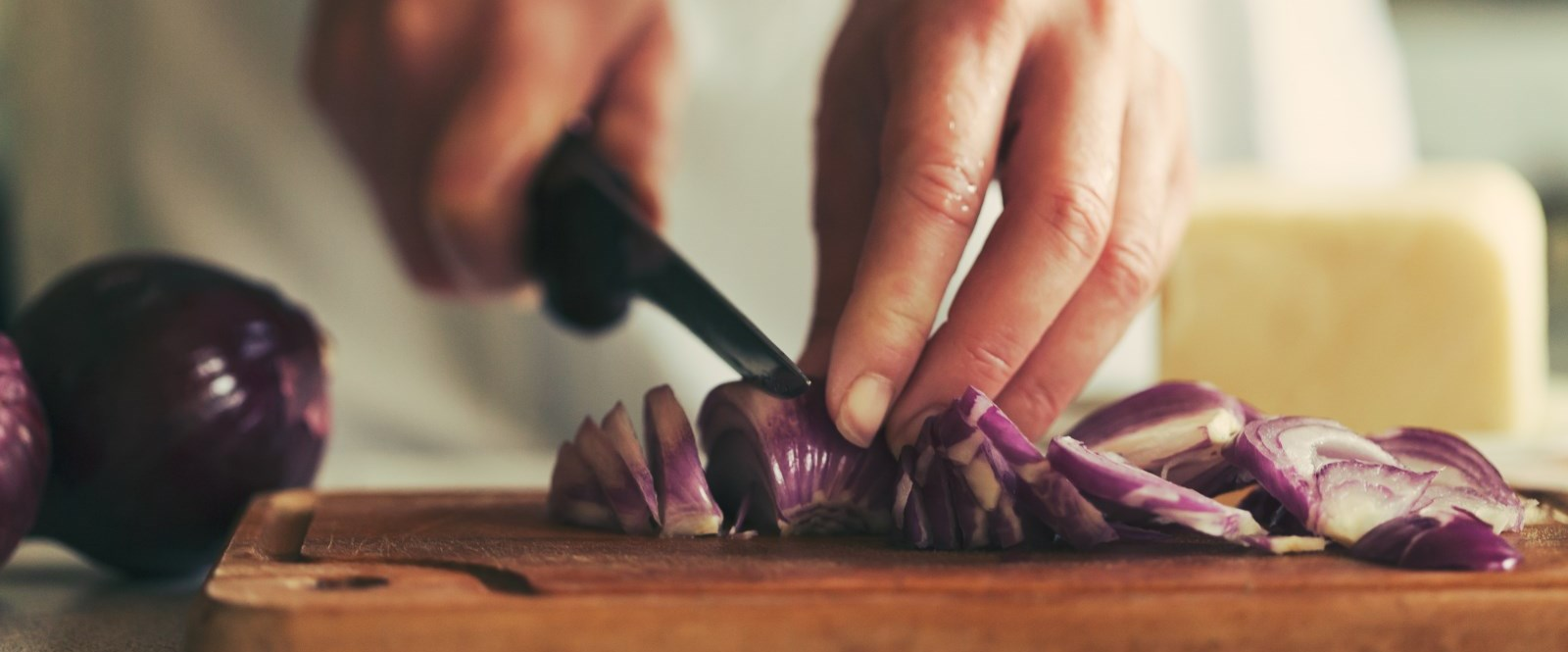 chef cutting red onion on wooden cuttingboard