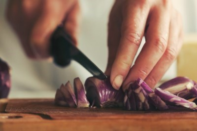 chef cutting red onion