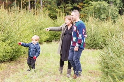 family out in field point to evergreen trees
