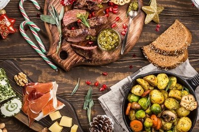 holiday table full of charcuterie boards displaying meat, cheese, candy canes and more