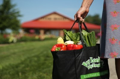 person hanging onto market bag in front of farmers' market
