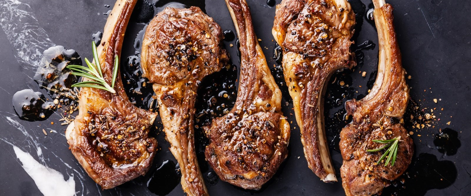 seasoned lamb chops on a marble slab with rosemary