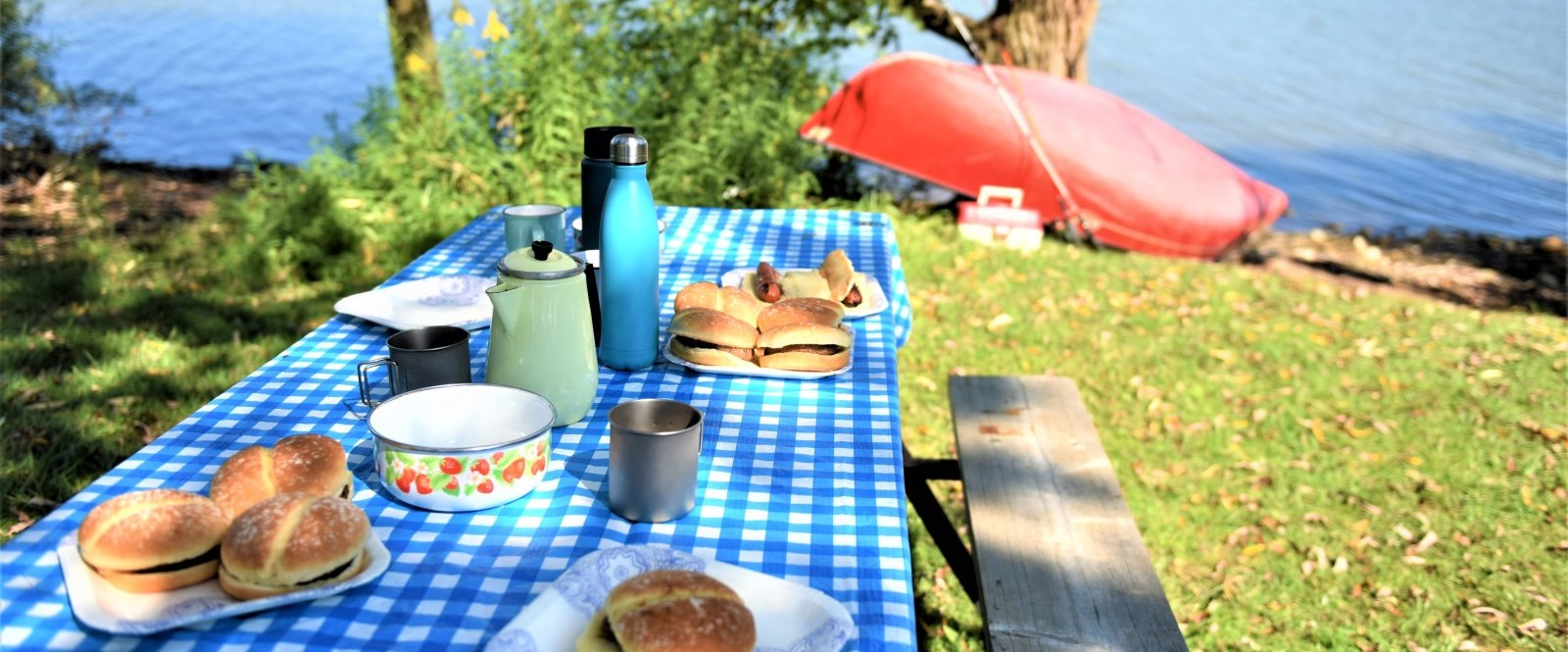 blue picnic table with pots and burgers near a lake