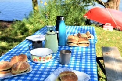 blue clothed picnic table overlooking lake and canoe