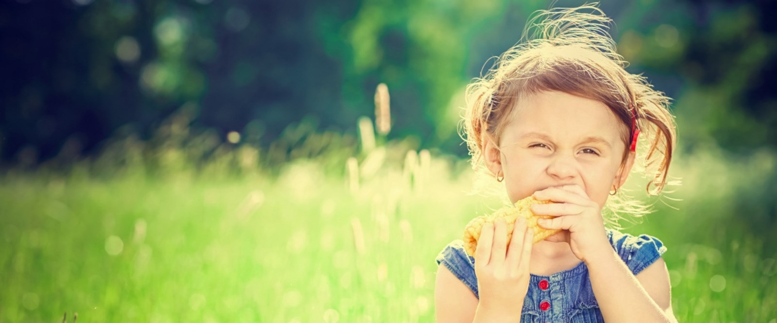 girl eating a corn of cob in a field