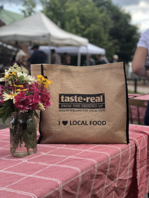 taste real bag with jar of flowers on a picnic table