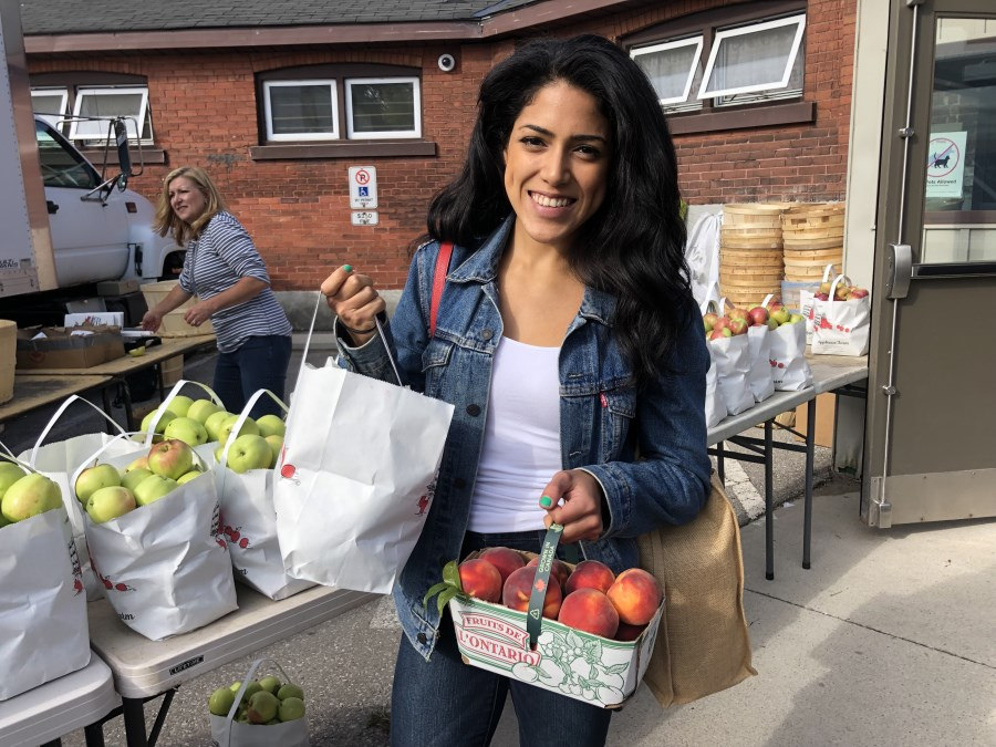 sassy tomato blogger holding a bag of apples and basket of peaches