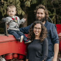 family of three infront of tractor