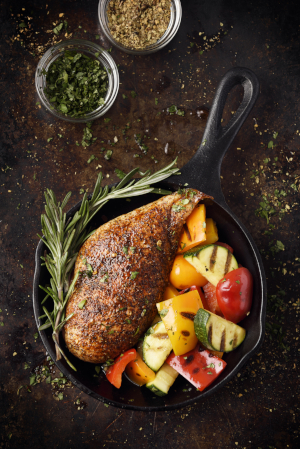 chicken breast in a skillet with roasted vegetables