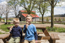 two boys sitting at a picnic table eating ice cream