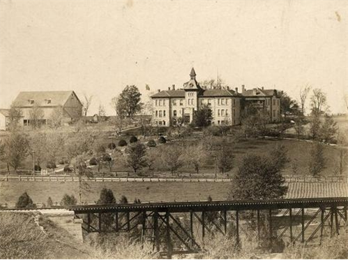 black and white photo of railroad bridge with house on hill in back