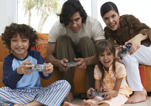 Family for 4 playing video games on a couch