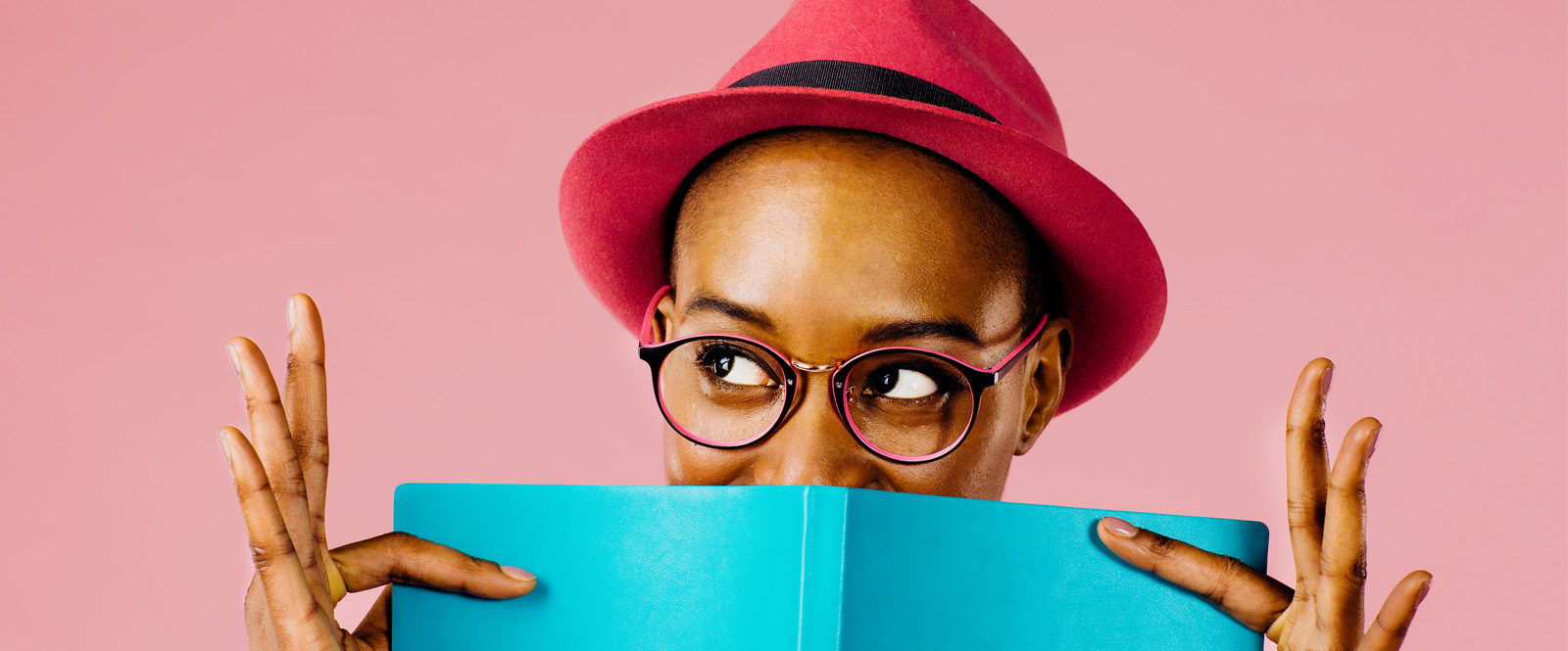 Woman wearing glasses peeking out from behind book