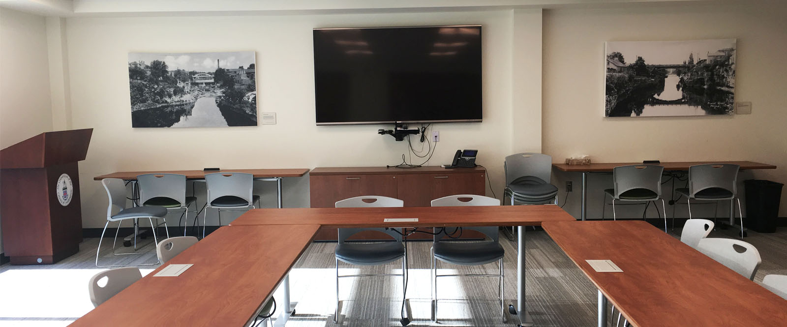 Meeting room with tables, chairs, and a TV