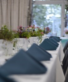 Head table set with blue linen napkins and fresh flowers