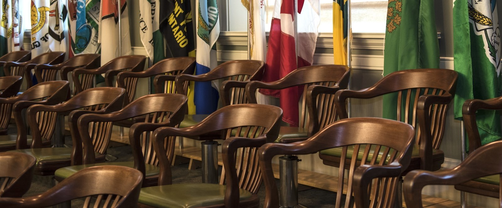 Wooden chairs in fron of row of flags