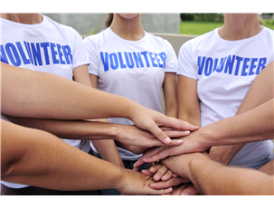 youth wearing volunteer shirts putting hands together