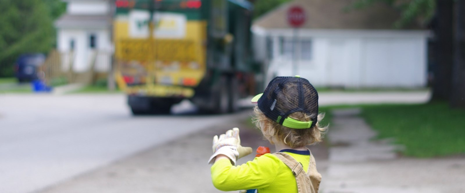 boy waving at garbage truck