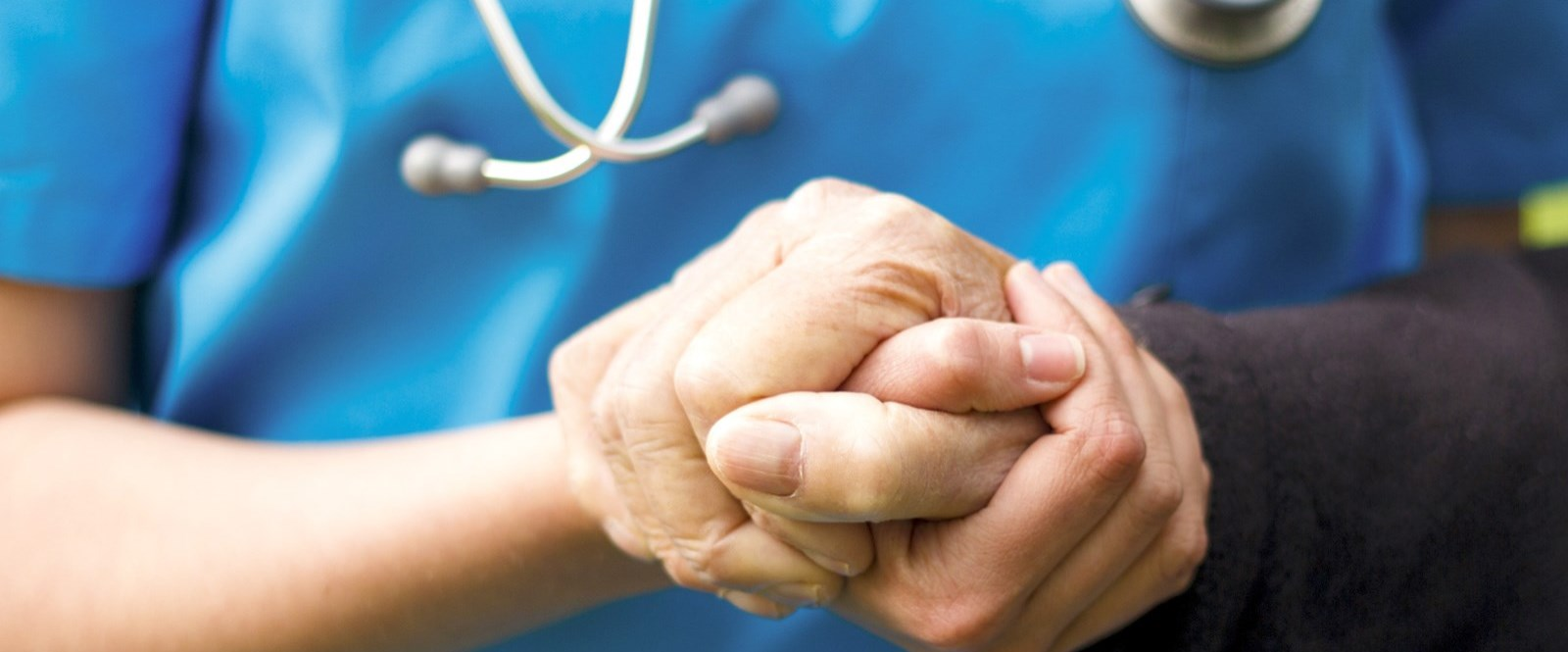 nurse holding senior hand