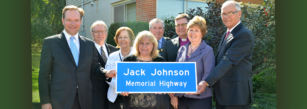 The Jack Johnson family posing with a blue road sign entitled Jack Johnson Memorial Highway