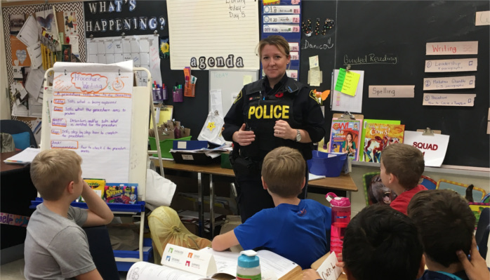 female officer in classroom with children
