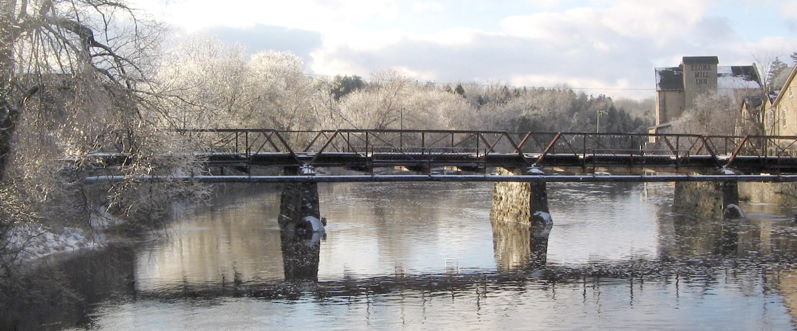 iron bridge over river in winter