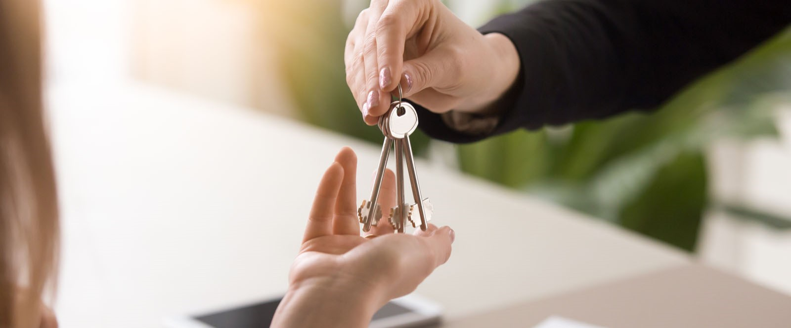person handing house keys to tenant