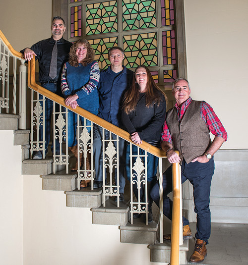 five staff members of the ERC standing on stair case